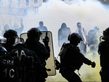 TOPSHOT - Protesters stand in tear gas smoke as they face police during clashes on the Invalides esplanade at a demonstration in Paris, on June 16, 2020, as part of a nationwide day of protests to demand better working conditions for health workers. (Photo by Alain JOCARD / AFP) (Photo …