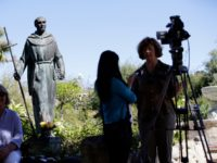 File - In this Sept. 23, 2015 file photo, an interview is conducted next to a statue of Junipero Serra at the Carmel Mission in Carmel-By-The-Sea, Calif. Northern California's Stanford University has announced it will drop the name of a controversial 18th century Spanish priest from two dormitories and its …