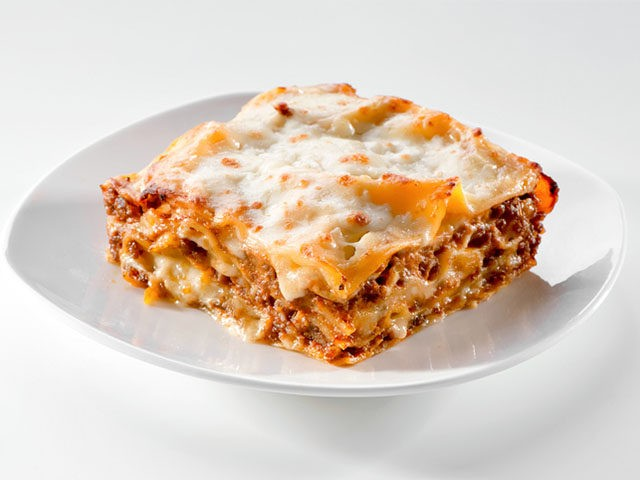 freshly baked lasagna piece on white plate close-up