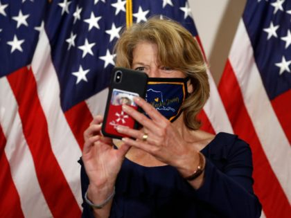Sen. Lisa Murkowski, R-Alaska, takes a selfie as she wears an Alaska-themed face mask to protect against the spread of the new coronavirus before attending a weekly Republican Senate luncheon on Capitol Hill in Washington, Tuesday, May 19, 2020. (AP Photo/Patrick Semansky)