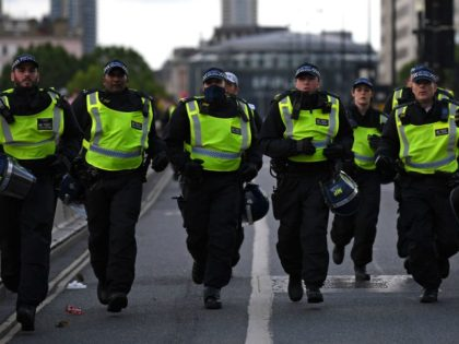 Police officers runs across Waterloo Bridge to reinforce colleagues on the Strand after protesters supporting the Black Lives Matter movement clash with opponents in central London on June 13, 2020, in the aftermath of the death of unarmed black man George Floyd in police custody in the US. - Police …