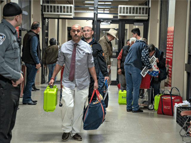Election officials carrying equipment during last month's presidential primary in El Paso. A Texas judge says he will allow all voters to apply for absentee ballots in light of the coronavirus pandemic. The state typically makes it difficult to cast such ballots. PAUL RATJE / AFP VIA GETTY IMAGES