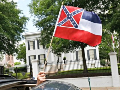 "In this April 25, 2020 photograph, a small Mississippi state flag is held by a participant during a drive-by ""re-open Mississippi"" protest past the Governor's Mansion, in the background, in Jackson, Miss. This current flag has in the canton portion of the banner the design of the Civil War-era Confederate …"