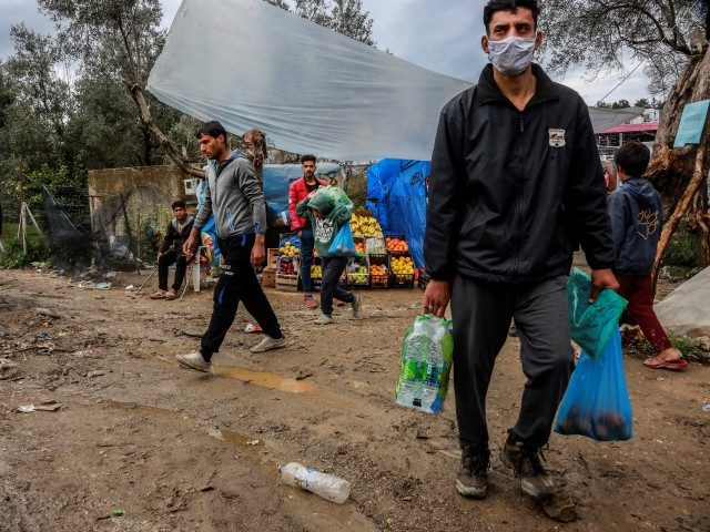 TOPSHOT - Migrants and refugees carry bags with food at a makeshift camp next to the Moria camp on the Greek island of Lesbos on April 2, 2020. - Over 20 coronavirus cases were found in a camp near Athens this week. At the camp of Moria on the island …
