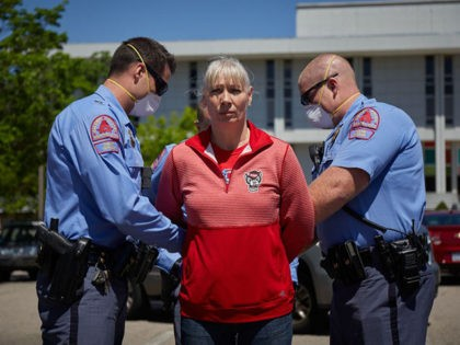 A protester from a grassroots organization called REOPEN NC is arrested after refusing to leave a parking lot during a demonstration against the North Carolina coronavirus lockdown at the North Carolina State Legislature in Raleigh, North Carolina, on April 14, 2020. - The group was demanding the state economy be …