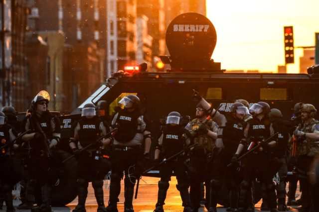 TOPSHOT - State patrol officers stand by a sheriff armored vehicule during a protest over the death of George Floyd on May 31, 2020 in Minneapolis, Minnesota. - Thousands of National Guard troops patrolled major US cities after five consecutive nights of protests over racism and police brutality that boiled …