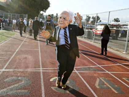 A supporter of US Democratic presidential candidate Bernie Sanders wears a mask during a rally at Santa Monica High School Football Field in Santa Monica, California, on May 23, 2016. Democratic presidential frontrunner Hillary Clinton on May 23 rejected an invitation to take part in a final campaign debate against …