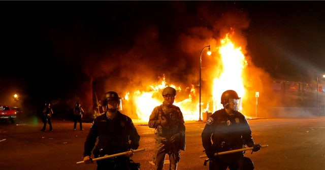Police guard against protesters fire background Minneapolis George Floyd riot ap 640x335.'