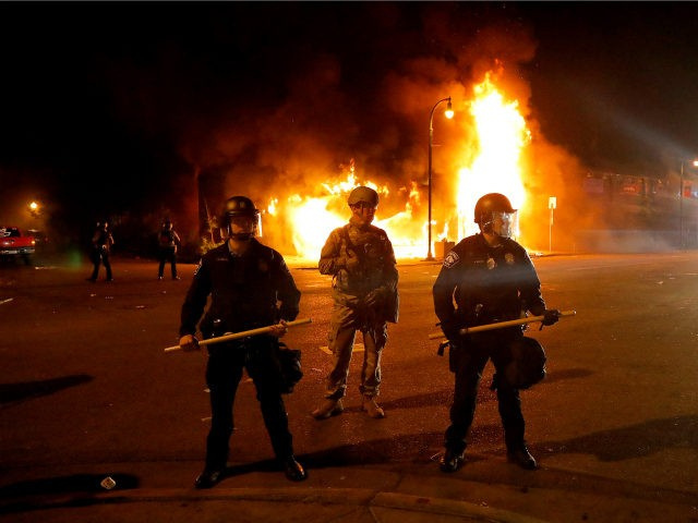 Minneapolis Police keep protesters back near a structure fire, Saturday, May 30, 2020, in Minneapolis. Protests continued following the death of George Floyd, who died after being restrained by Minneapolis police officers on Memorial Day. (AP Photo/Julio Cortez)