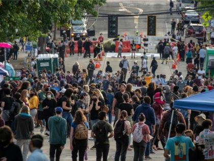 "People walk near the Seattle Police Departments East Precinct in the so-called ""Capitol Hill Autonomous Zone"" on June 10, 2020 in Seattle, Washington. The zone includes the blocks surrounding the Seattle Police Departments East Precinct, which was the site of violent clashes with Black Lives Matter protesters, who have continued …"