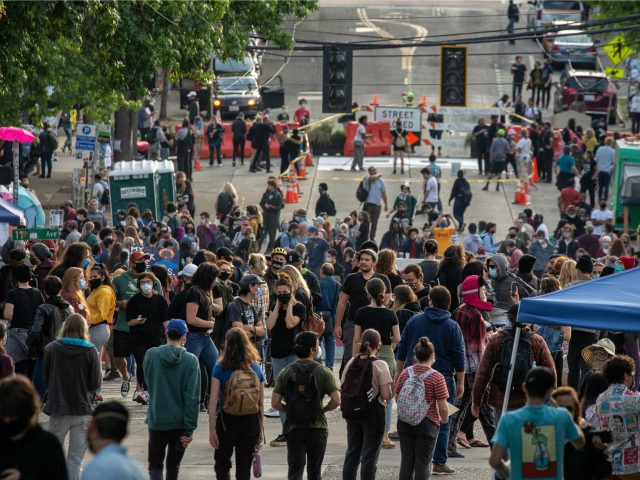 """People walk near the Seattle Police Departments East Precinct in the so-called """"Capitol Hill Autonomous Zone"""" on June 10, 2020 in Seattle, Washington. The zone includes the blocks surrounding the Seattle Police Departments East Precinct, which was the site of violent clashes with Black Lives Matter protesters, who have continued …"""