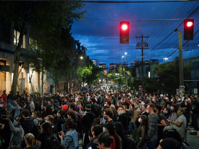"People listen as a band plays a free show in front of the Seattle Police Departments East Precinct in the so-called ""Capitol Hill Autonomous Zone"" on June 10, 2020 in Seattle, Washington. The zone includes the blocks surrounding the Seattle Police Departments East Precinct, which was the site of violent …"