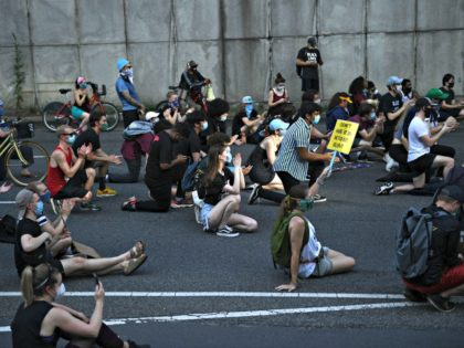 "Demonstrators sit on a highway to block it, as protests triggered by the death of George Floyd while in police custody, continue on June 23, 2020, in Washington, DC. - US President Trump on his way to Arizona warned that protesters who attempted to establish an ""autonomous zone"" in the …"