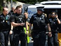 Police officers congregate outside a cordoned off block of flats where the suspect of a multiple stabbing incident lived in Reading, west of London, on June 23, 2020. - British counter-terrorism police have been given until June 27 to question a suspect widely identified as Libyan Khairi Saadallah in an …