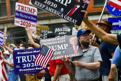 Supporters of of President Donald Trump hold signs during a rally at Pliny Park in Brattleboro, Vt., Saturday, June 27, 2020. (Kristopher Radder/The Brattleboro Reformer via AP)