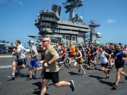 In this May 24, 2020, photo, provided by the U.S. Navy Sailors run on the flight deck aboard the aircraft carrier USS Dwight D. Eisenhower (CVN 69). When coronavirus made U.S. Navy ship stops in foreign countries too risky, the USS Dwight D Eisenhower and the USS San Jacinto were …