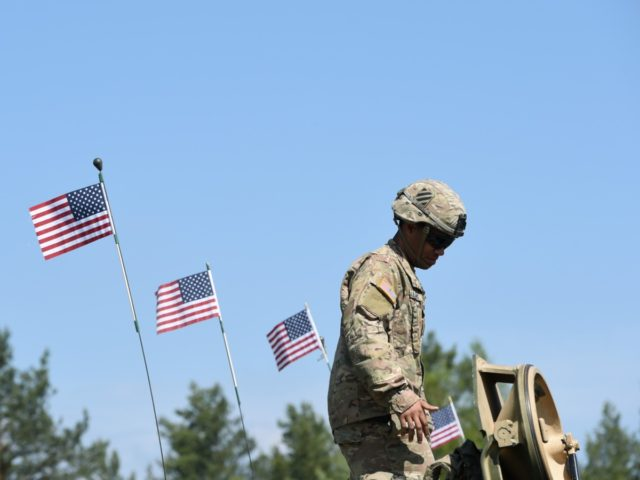 """A US soldier stands at a tank type """"M1A2 SEP"""" which are decorated with US flags at a parking position at the training area in Grafenwoehr, near Eschenbach, southern Germany, on May 11, 2016, during the exercise """"Strong Europe Tank Challenge 2016"""". The exercise is the first Europe-wide tank challenge …"""