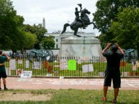 People visit Lafayette Park where protest signs are seen along the fencing that surrounds a statue of President Andrew Jackson, Tuesday, June 16, 2020, near the White House in Washington, where protests have occurred over the death of George Floyd, a black man who was in police custody in Minneapolis. …