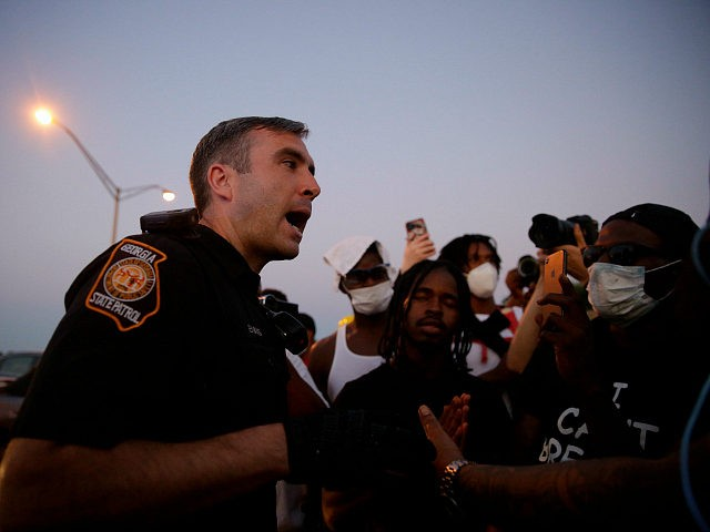 An official talks with protesters on Saturday, June 13, 2020, near the Atlanta Wendy's where Rayshard Brooks was shot and killed by police Friday evening following a struggle in the restaurant's drive-thru line in Atlanta. (AP Photo/Brynn Anderson)