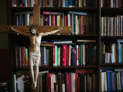BIRMINGHAM, ENGLAND - AUGUST 11:A crucifx leans against religious academic books at Oscott College on May 8, 2014 in Birmingham, England. St. Mary's College, Oscott opened in 1794 and was designed by the gothic architect Augustus Welby Pugin. The formation for catholic priesthood takes six years living in the college …