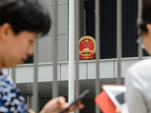 People use their phones to play the Pokemon Go app outside the Legislative Council offices in Hong Kong on July 26, 2016. The Chinese army garrisoned in Hong Kong has warned people searching for Pikachu and other virtual monsters to stay off their premises, as Pokemon Go mania sweeps the …