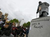"LONDON, UNITED KINGDOM - JUNE 07: Protesters raise their fists in Parliament Square Garden around the statue of Winston Churchill which has graffiti with the words ""was a racist"" outside the Houses of Parliament in Westminster during a Black Lives Matter protest on June 07, 2020 in London, United Kingdom. …"