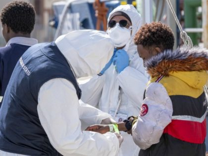 An Italian police agent wearing protective suit and mask puts a bracelet on a man as migrant rescued in the Mediterranean as they disembark from the Sea Watch NGO's ship on February 27, 2020 in the port of Messina, Sicily. - Migrants are checked for COVID-19 as they disembark from …