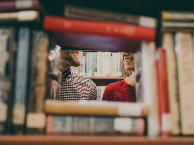 Man and woman's partial faces as they are seen smiling through books at a library.