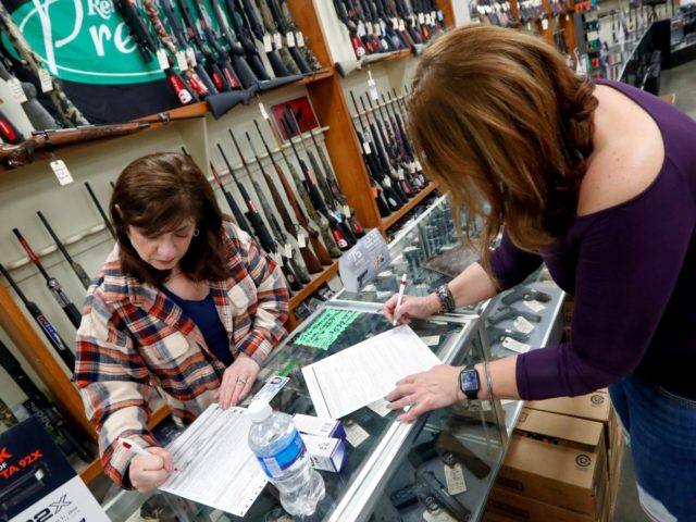 Andrea Schry, right, fills out the buyer part of legal forms to buy a handgun as shop worker Missy Morosky fills out the vendors parts after Dukes Sport Shop reopened, Wednesday, March 25, 2020, in New Castle, Pa. under the new conditions specified for gun stores. The store had closed …