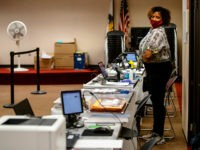 A poll worker wearing a protective mask is seen at the Dunwoody Library on Monday, May 18, 2020, in Dunwoody, Georgia. Georgians were greeted with a few new procedures as they participated in the first day of in-person early voting for the state's June 9 primaries with the coronavirus pandemic …