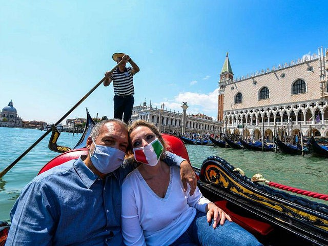People enjoy a gondola ride past the Doge's Palace on May 29, 2020 in Venice, as the country eases its lockdown aimed at curbing the spread of the COVID-19 infection, caused by the novel coronavirus. (Photo by ANDREA PATTARO / AFP) (Photo by ANDREA PATTARO/AFP via Getty Images)