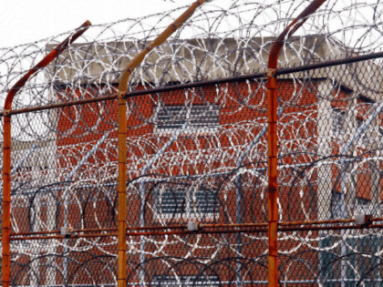 In this March 16, 2011, file photo, a security fence surrounds inmate housing on the Rikers Island correctional facility in New York. Health experts say prisons and jails are considered a potential epicenter for America's coronavirus pandemic. (AP Photo/Bebeto Matthews, File)
