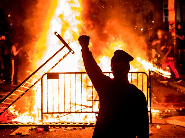 TOPSHOT - A protester raises a fist near a fire during a demonstration outside the White House over the death of George Floyd at the hands of Minneapolis Police in Washington, DC, on May 31, 2020. - Thousands of National Guard troops patrolled major US cities after five consecutive nights …