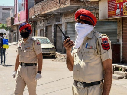 Police personnelstand guard as they close a street near the location of the residence of Sikh spiritual singer Nirmal Singh Khalsa, who died of the coronavirusafter being tested positive, during a government-imposed nationwide lockdown as a preventive measure against the COVID-19 coronavirus, in Amritsar on April 2, 2020. (Photo by …