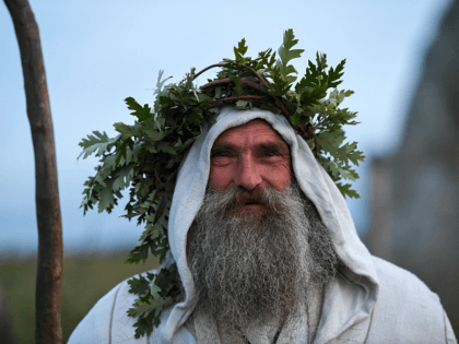 WILTSHIRE, ENGLAND - JUNE 20: A druid named Merlin is seen at Stonehenge as the sun sets ahead of Summer Solstice on June 20, 2020 in Amesbury, United Kingdom. English Heritage, which manages the site, said 'Our priority is always to ensure the safety and wellbeing of staff, volunteers, attendees …