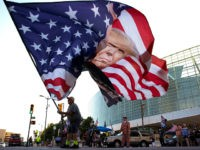 TULSA, OKLAHOMA - JUNE 18: Trump supporter Randall Thom waves a giant Trump flag to passing cars outside the BOK Center June 18, 2020 in Tulsa, Oklahoma. Trump is scheduled to hold his first political rally since the start of the coronavirus pandemic at the BOK Center on Saturday while …