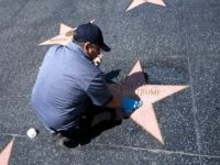 A maintenance worker uses cleaning product to remove graffiti after Donald Trump's star on the Hollywood Walk of Fame was defaced, in a mostly empty Hollywood, California, April 23, 2020, during the coronavirus COVID-19 pandemic. (Photo by Robyn Beck / AFP) (Photo by ROBYN BECK/AFP via Getty Images)