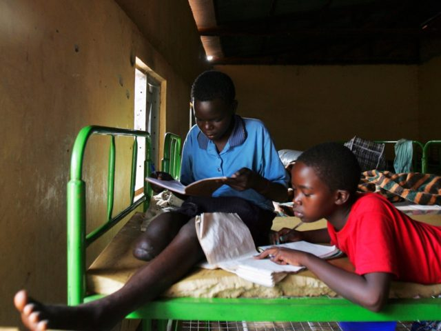 GULU, UGANDA - DECEMBER 10: Former abductees, thirteen year-old Joyce Apio (L), and eight year-old Mary Acan, do their homework at The World Vision Children of War Rehabilitation Center on December 10, 2005 in Gulu, Uganda. Shortly after her abduction at the hands of the Lord's Resistance Army (LRA), Joyce …