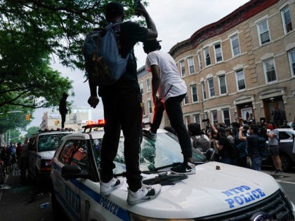 Protesters jump on an NYPD police SUV during a demonstration against the killing of George Floyd by Minneapolis police on Memorial Day on May 30, 2020 in the Borough of Brooklyn in New York. - Demonstrations are being held across the US after George Floyd died in police custody on …