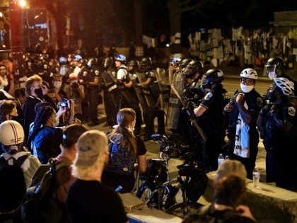 Protesters confront a row of police officers during demonstrations at Lafayette square, in front of the White House, in Washington, DC on June 22, 2020, where earlier protesters tried to bring down the equestrian statue of former US President General Andrew Jackson. - The United States is grappling with widespread …