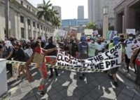 Protesters cross over a barricade as they march in front of the Federal Detention Center, in the death of George Lloyd, Sunday, May 31, 2020, in Miami. (AP Photo/Wilfredo Lee)