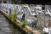 Customers seated in small glasshouses enjoy lunch at the Mediamatic restaurant in Amsterdam, Netherlands, Monday, June 1, 2020. The government took a major step to relax the coronavirus lockdown, with bars, restaurants, cinemas and museums reopening under strict conditions, abiding by government guidelines and respecting social distancing to help curb …