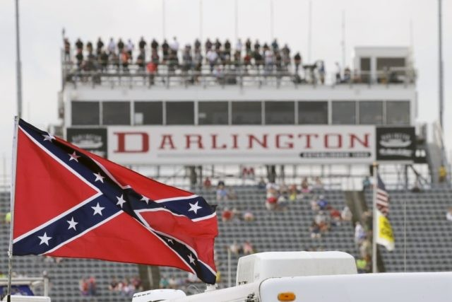 In this Sept. 5, 2015, file photo, a Confederate flag flies in the infield before a NASCAR Xfinity auto race at Darlington Raceway in Darlington, S.C. Bubba Wallace, the only African-American driver in the top tier of NASCAR, calls for a ban on the Confederate flag in the sport that …