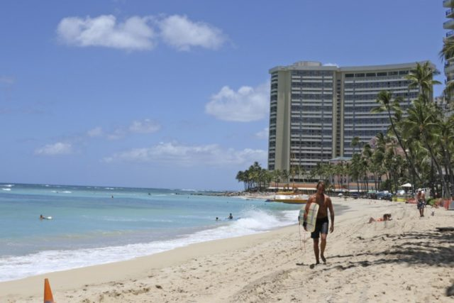 In this photo taken Friday, June 5, 2020, a surfer walks on a sparsely populated Waikiki beach in Honolulu. Hawaii faces unpleasant options for addressing a dramatic decline in tax revenues precipitated by the coronavirus pandemic and the shutdown of the state's tourism industry. (AP Photo/Audrey McAvoy)