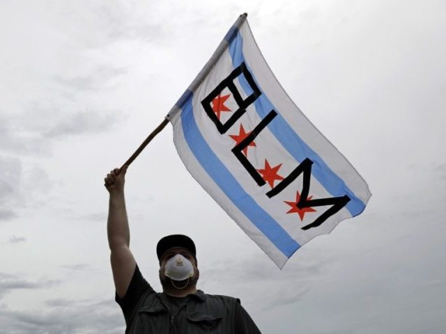 In this June 3, 2020, file photo, a protester waves a city of Chicago flag emblazoned with the acronym BLM for Black Lives Matter, outside the Batavia, Ill., City Hall during a protest over the death of George Floyd. Black Lives Matter has gone mainstream — and black activists are …