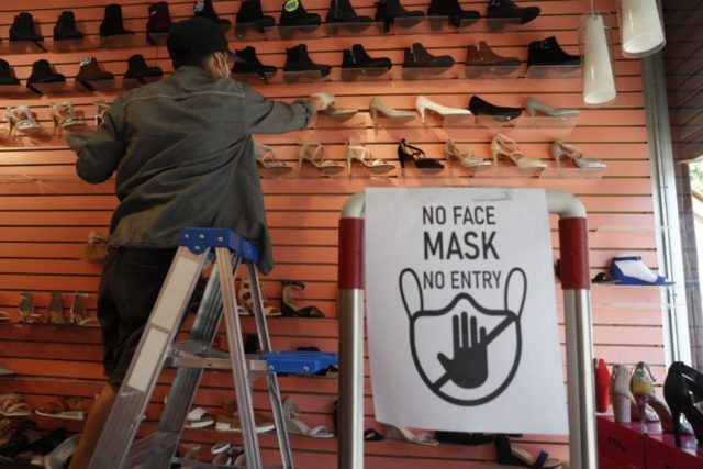 Manager Angel Ramos arranges shoes on a display in Top shoes, Monday, June 8, 2020, in the Brooklyn borough of New York, after retail stores were allowed to reopen to customers on the first day marking Phase 1 reopening for New York City. In a city famous for its lack …