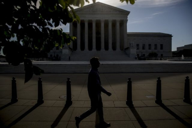 In this May 4, 2020, file a man walks past the Supreme Court in Washington. (AP Photo/Andrew Harnik, File)
