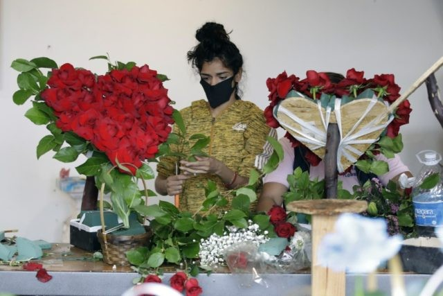 In this May 10, 2020, file photo, a merchant prepares a floral arrangement on Mother's Day at the Los Angeles Flower Market in Los Angeles. Americans are more unhappy today than they've been in nearly 50 years. That's according to the COVID Response Tracking Study, conducted in late May by …