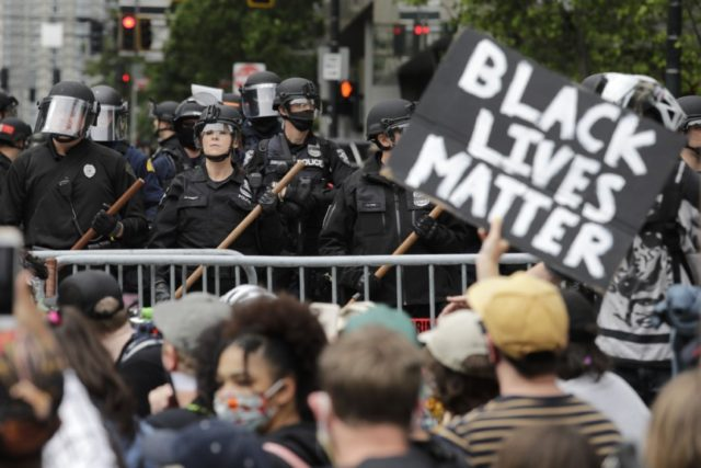 In this June 3, 2020, file photo, police officers behind a barricade look on as protesters fill the street in front of Seattle City Hall, in Seattle, following protests over the death of George Floyd, a black man who was in police custody in Minneapolis. The King County Labor Council, …