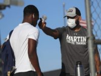 Before entering the field gates for football strength and conditioning camp at Arlington Martin High School, athletic Trainer Joey Pena, right, uses a thermometer on the forehead of sophomore running back Gervawn Neville for a temperature check Thursday, June 18, 2020, in Arlington, Texas. While states have been easing the …